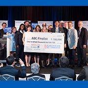 Des représentants d'Anixter et de la ville de Statesboro tiennent un chèque au montant de 100000$ remis à la ville pour leur participation à la ronde finale. Image